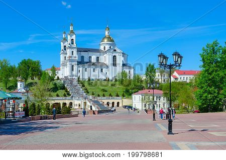 VITEBSK BELARUS - MAY 23 2017: Unidentified people go on Pushkin bridge in the direction of Holy Dormition Cathedral and Holy Spirit convent Vitebsk Belarus