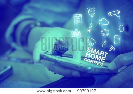 Close up woman using mobile phone with Smart home control word and icon features Digital lifestyle conceptDuotone color filtered.