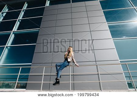 A Hipster Girl Sits On A Railing And Shows Long Legs And Blue Jeans