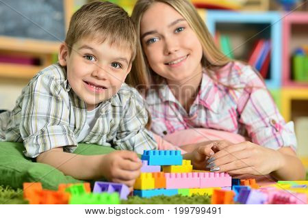 Brother and sister playing with colorful plastic blocks