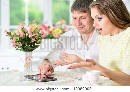 young couple sitting at table and looking at digital tablet
