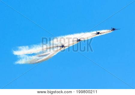 Group Of White Turboprop Airplane With A Trace Of White Smoke Against A Blue Sky