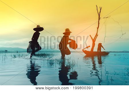 Children boy and girl catching fish Fisherman fishing nets job lifestyle on boat at lake river sunset thailand silhouette.