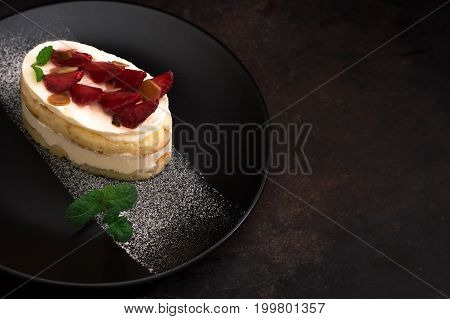 Strawberry cake with almond petals. Old black background. Close-up. Top view. Close-up