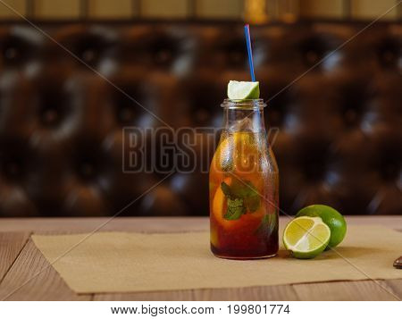 A moist glass bottle of a cool cocktail or beverage, green slices of lime, yellow fragrant lemon, verdant leaves of mint on a wooden table on a blurred brown background.