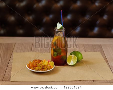 A bottle of cocktail with slices of lemon and leaves of mint, green fragrant pieces of lime, a plate with dried apricots and raisins on a blurred brown table background.