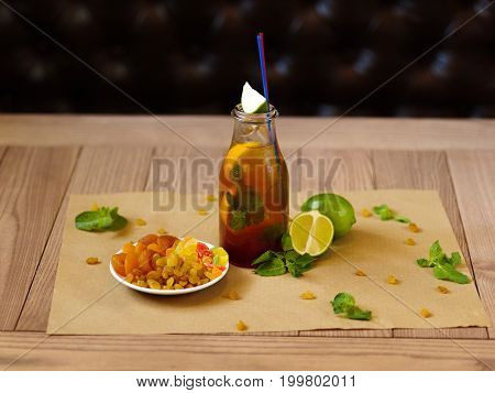 A wooden table with green leaves of mint, a bottle of cocktail with slices of lemon, fresh pieces of lime, a plate with dried apricots and raisins on a blurred brown background.
