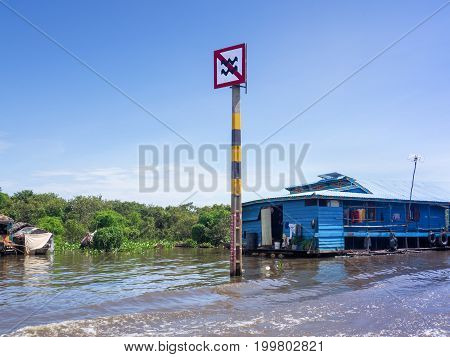 Boat traffic sign at Tonle Sap Lake, Siem Reap, Cambodia, caution about not creating high wave in community district by controlling the speed of the boat