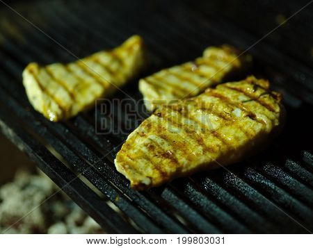 Macro picture of tasty juicy pieces of grilled chicken. Fried nutritious meat on a black grid background. Tender smoky fillets of meat. Outdoors, nature, cooking concept. Copy space.