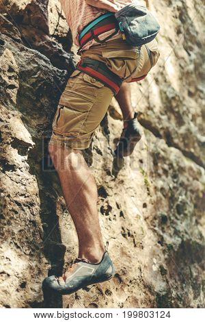 Adult Male Mountaineer In Safety Harness Climbs A Rock Wall. Extreme Hobby Outdoor Activity Concept