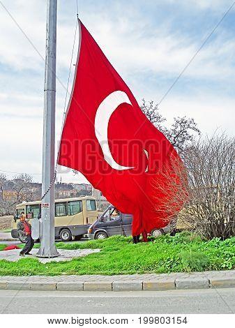 ISTANBUL, TYRKEY - MARCH, 10 2008: Unidentified man raises the Turkey flag, Istanbul, Turkey