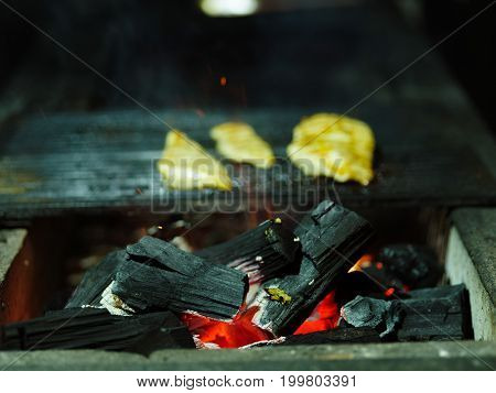 Close-up of grilling process. Glowing firewood next to three juicy pieces of grilled chicken. Tender smoky fillet on a blurred background. Outdoors, nature, cooking concept. Copy space.