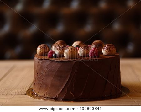 A light wooden table with appetizing chocolate pie sprinkled with cocoa and decorated with raspberries and black currants on a brown blurred background.