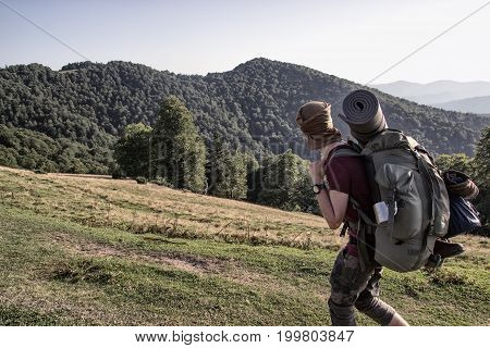 A soldier with a backpack is walkingi in the mountains