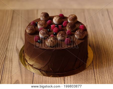 A wooden table with a sweet chocolate cake, adorned with raspberries and blackcurrants, sprinkled with cocoa powder on a light wooden background.