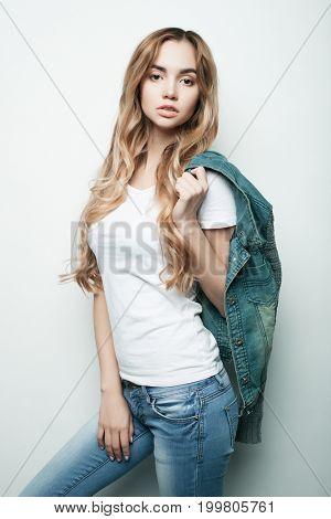 Young fashion model posing in studio, white background