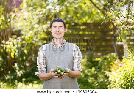 Guy holding cucumbers in palms