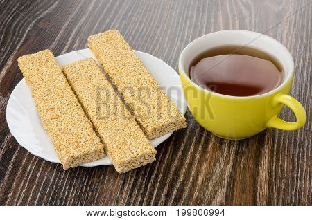 Cup Of Tea And Kozinaki With Sesame On Wooden Table