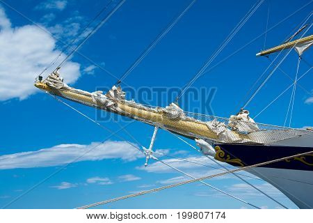 Bowsprit of big sailing vessel. Sky and clouds in background.