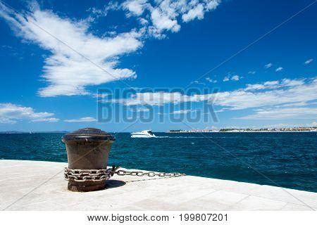 Iron bollard with chain on quay in port in Zadar in Croatia.