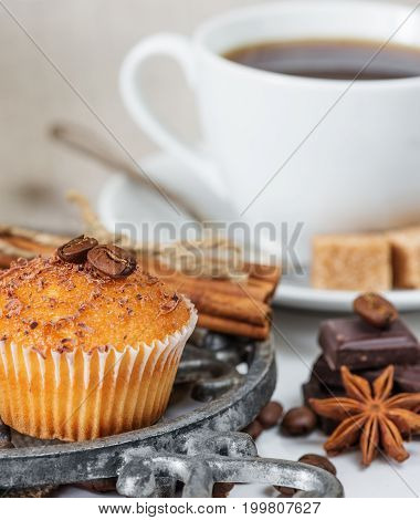 Cupcakes with chocolate shavings surrounded by coffee beans and a variety of spices