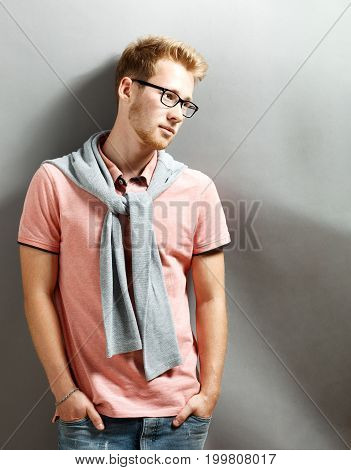 Handsome young blonde man on grey background.