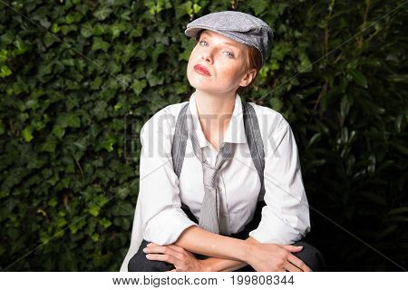 young red-haired woman as a man dressed in the garden makes on macho
