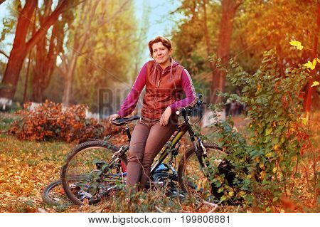 Woman enjoys riding a bicycle in autumn park