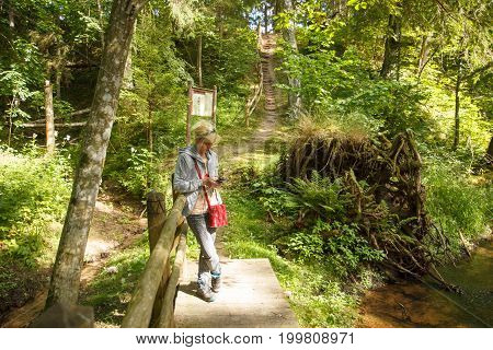 A woman standing on a small wooden bridge in a foresty area