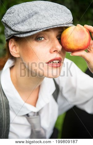 red-haired woman with cap in the garden holds apple before the eye