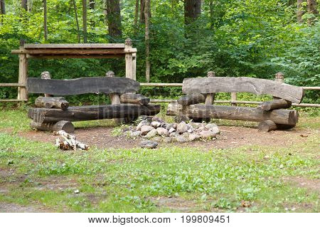 A fireplace with two wooden benches in a park