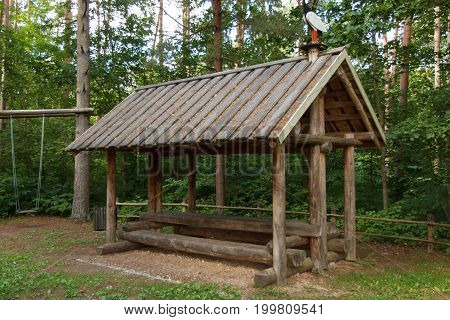 A wooden hut with a table and benches