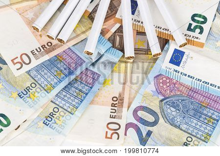 20 and 50 Euro banknotes bills cash with cigarettes. Concept of cost of tabacco cigarettes.