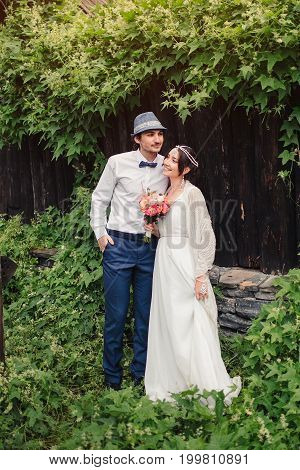 Boho wedding. beautiful couple kissing on grass and wooden background