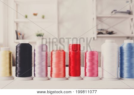 Colorful thread spools on wooden table close up. Sewing string, copy space for text. Art, handicraft concept