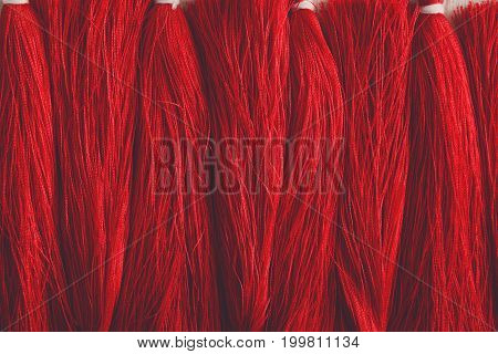 Red tassels line close up. Woman handicraft. Art, creativity, hobby, home workshop concept