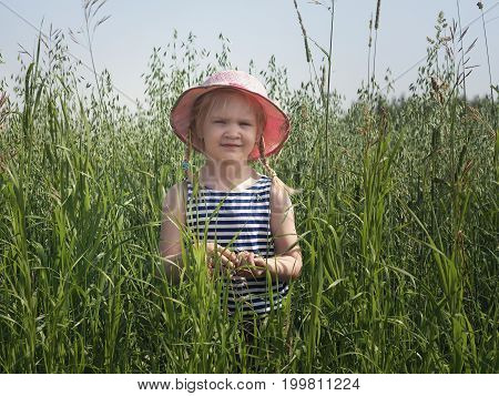 The child in the field. Tall spikelets of oats. The girl in the hat. Portrait