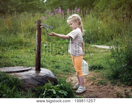 Little girl collects water in the canister. Rustic column well