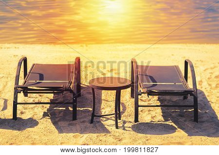 Romantic holiday vacation concept. Pair of sun loungers and a table on a deserted beach with sun during sunset