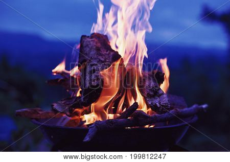 Outdoor night scene of grill with burnt wood close-up view.
