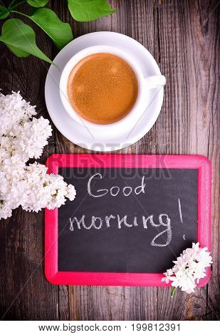 white cup with coffee and a black chalk board with an inscription good morning on a gray wooden background