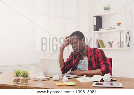 Pensive african-american employee in office. Thinking over new project