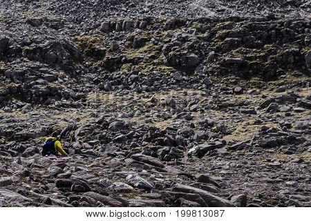 Walker In Yellow Traversing A Rock Field In Scottish Highlands