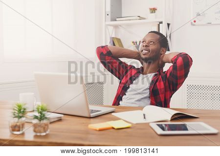 Relaxed black businessman in casual working with laptop in modern white office interior