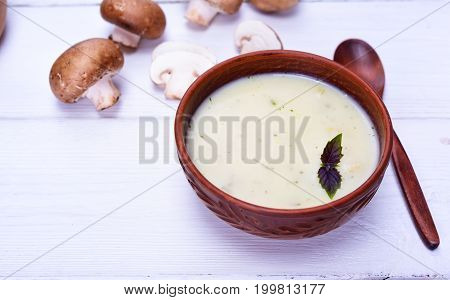 Mushroom creamy soup in a clay brown plate with a wooden spoon on a white table empty space on the left