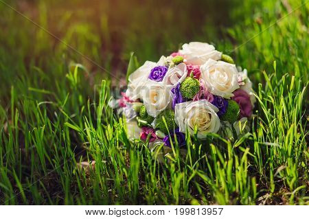 The bride's bouquet lying on bright green grass