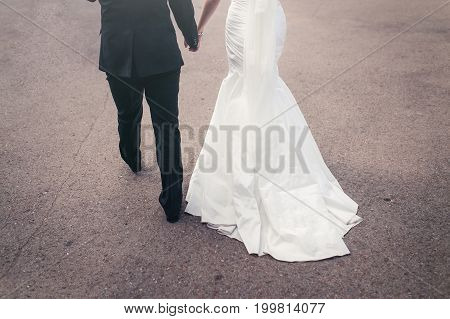 The Bride And Groom Walking Holding Hands