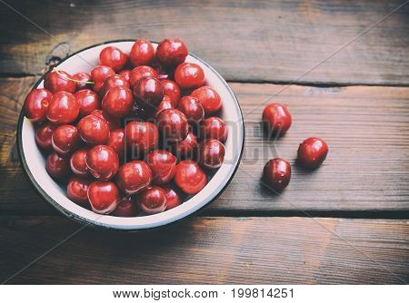 Ripe red cherry in an iron plate on a brown table vintage toning