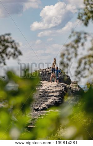 Lilienstein Germany - August 14 2017. A young climber with a muscular body makes a handstand on the top. Climber in Saxon Switzerland Lilienstein rock Germany.