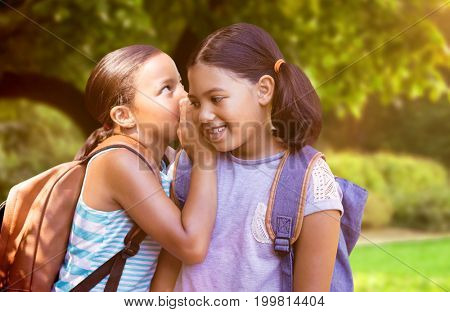 Student with backpack whispering in friend ear against trees and meadow in the park